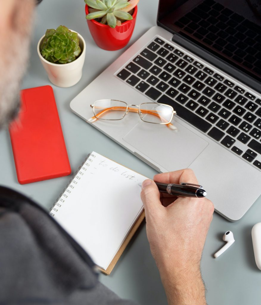Man writing TO DO LIST near laptop on a grey office desk close up